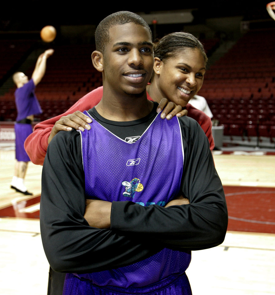 Photo - New Orleans Hornets guard Chris Paul poses for publicity photos with Oklahoma's Courtney Paris, right, following a Hornets team practice in Norman, Okla., Thursday, Jan. 12, 2006. The Hornets will play against the Sacramento Kings on Friday in Norman. Both players share the same nickname, CP3. Hornets' Maciej Lampe, of Poland, shoots at rear.  (AP Photo/Sue Ogrocki)