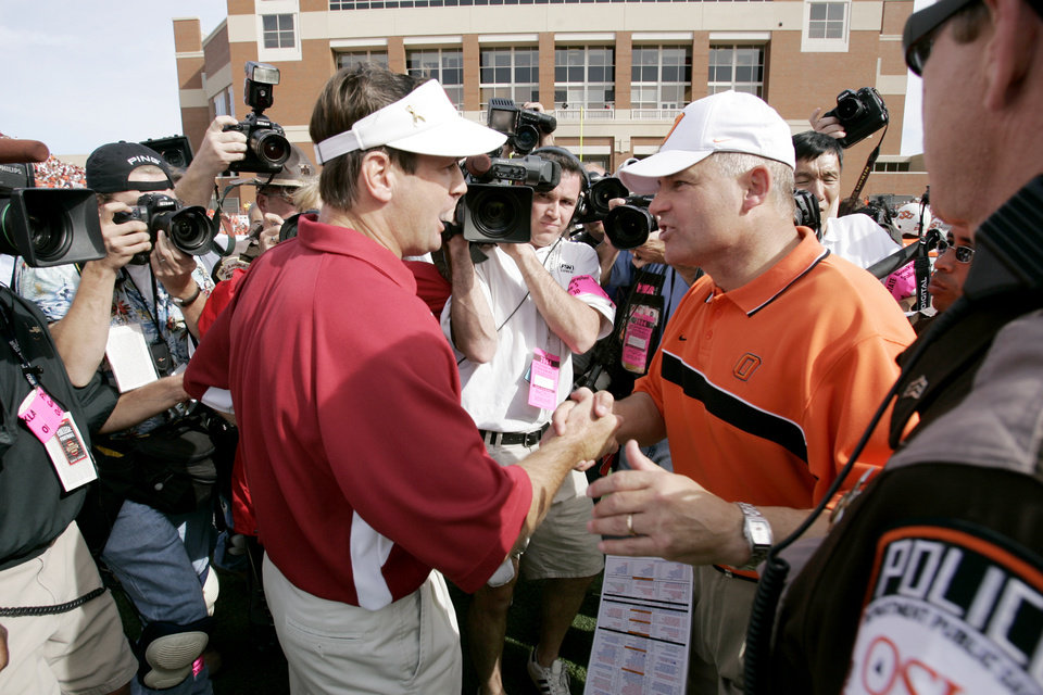 Photo - Stillwater, Okla. - October 30, 2004. University of Oklahoma (OU) at Oklahoma State University (OSU) Bedlam college football in Boone Pickens Stadium.   Coaches Bob Stoops and Les Miles  shake hands after the game.   By Doug Hoke/The Oklahoman