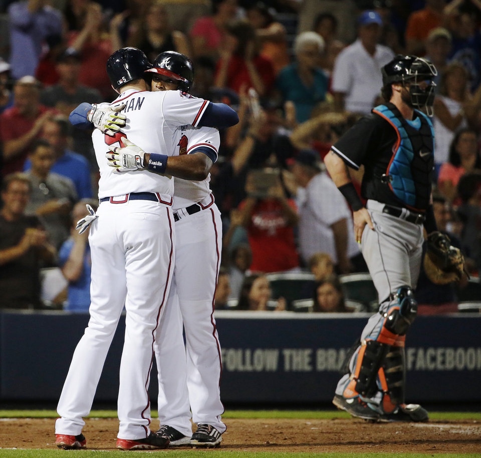Photo - Atlanta Braves' Justin Upton, center, embraces teammate Freddie Freeman, left, after Upton hit a two-run home run to score them both as Miami Marlins catcher Jarrod Saltalamacchia, right, stands at the plate in the sixth inning of a baseball game, Friday, Aug. 29, 2014, in Atlanta. (AP Photo/David Goldman)