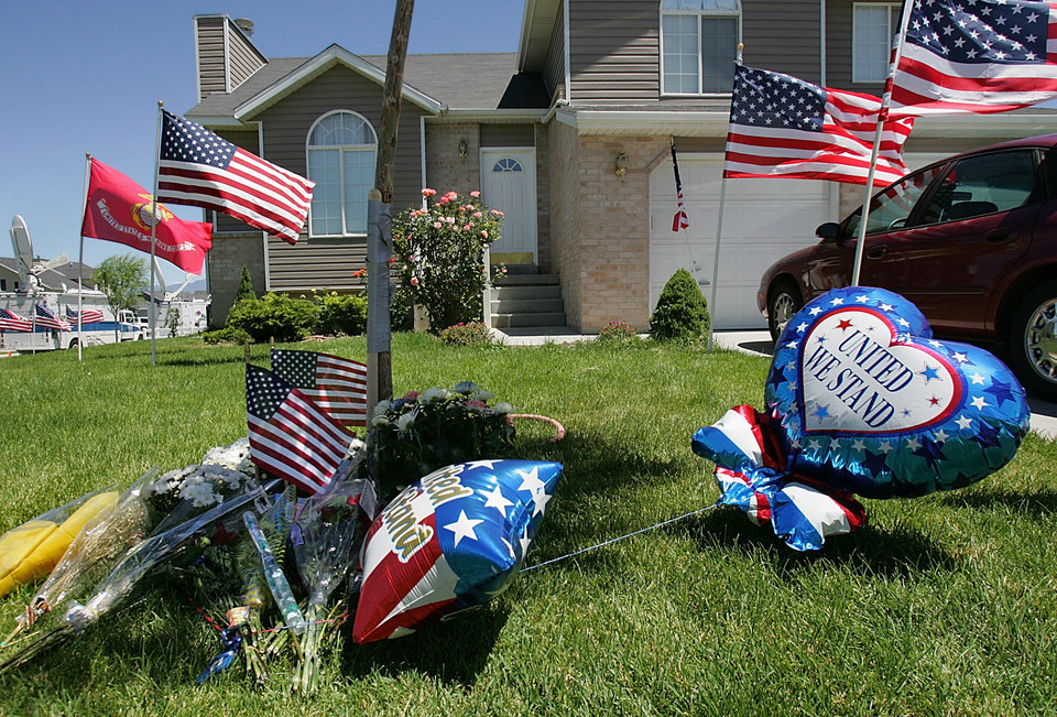 Photo - FILE - This July 5, 2004, file photo shows flowers and balloons scattering the lawn at the home of relatives of U.S. Marine Cpl. Wassef Ali Hassoun in West Jordan, Utah. Nearly 10 years ago Hassoun was declared a deserter after allegedly faking his own kidnapping in Iraq, then reappeared and was to face charges. But he disappeared again in 2005 after a visit home to Utah, has now turned himself in to U.S. authorities, and is being flown to the U.S. Sunday, June 29, 2014, from an undisclosed Mideast location. Once at Camp Lejeune, the commander of the 2nd Marine Expeditionary Force will determine whether to court-martial him.  (AP Photo/Douglas C. Pizac)