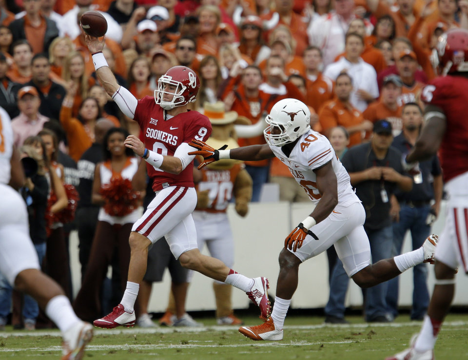 Photo - Oklahoma's Trevor Knight (9) gets rid of the ball in front of Texas' Naashon Hughes (40) during the Red River Showdown college football game between the University of Oklahoma Sooners (OU) and the University of Texas Longhorns (UT) at the Cotton Bowl in Dallas on Saturday, Oct. 11, 2014. 
