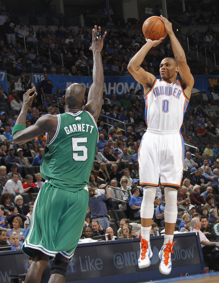 Photo - Oklahoma City Thunder point guard Russell Westbrook (0) shoots the ball over Boston Celtics power forward Kevin Garnett (5) during the NBA basketball game between the Oklahoma City Thunder and the Boston Celtics at the Chesapeake Energy Arena on Wednesday, Feb. 22, 2012 in Oklahoma City, Okla.  Photo by Chris Landsberger, The Oklahoman