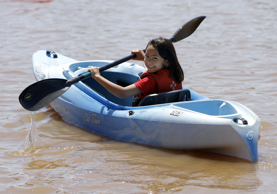 Photo - Kelly Woolum, 9, of Edmond, Okla., smiles at her mom as she tries a kayak during the Paddle Now! Youth Experience on the Oklahoma River,  Saturday, April 21, 2012. Photo by Sarah Phipps, The Oklahoman.