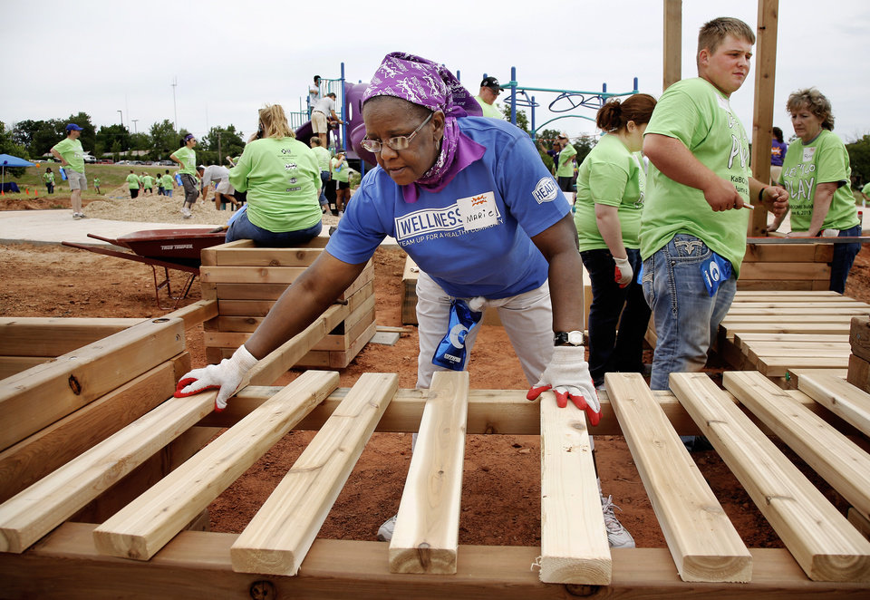 Marie Hopkins spaces planks evenly atop two supports to make a platform on the playground equipment.   Organizers said about 140 volunteers from Partners in Public Health, Blue Cross and Blue Shield of Oklahoma, organizers from KaBOOM! and residents of the Oklahoma City community will provided the labor on Saturday, June 8, 2013, to build a new playground at the Northeast Regional Health and Wellness Center on NE 63 Street, east of MLK Blvd.  The new playground's design is based on drawings created by children who participated in a Design Day event in April.   Photo  by Jim Beckel, The Oklahoman.