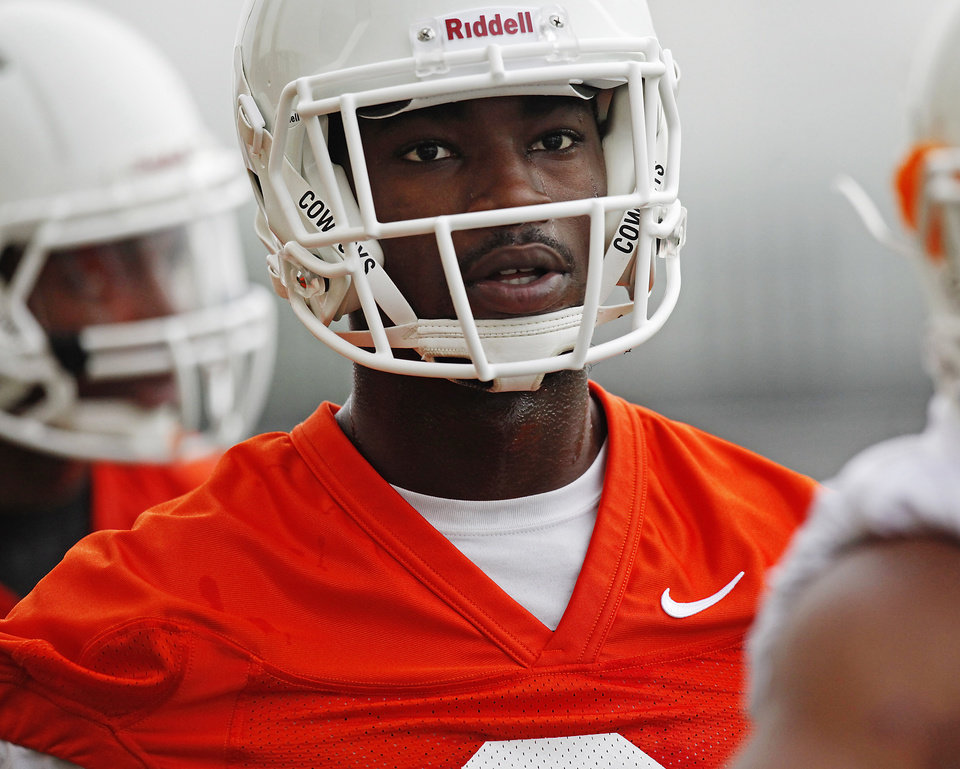 Photo - Oklahoma State wide receiver C.J. Curry (8) watches teammates run during the first team practice of the fall at the Sherman E. Smith Training Facility on the campus of Oklahoma State University in Stillwater on August 1, 2014. Photo by KT King, The Oklahoman