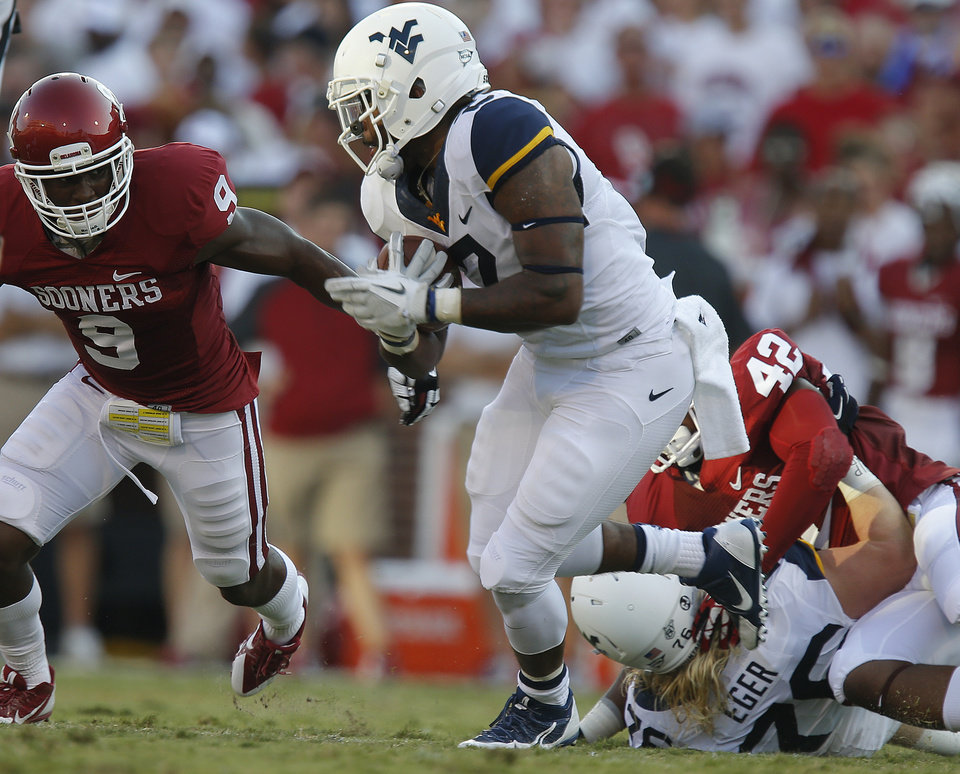 Photo - West Virginia's Dreamius Smith (2) runs by Oklahoma's Gabe Lynn (9) for a touchdown during a college football game between the University of Oklahoma Sooners (OU) and the West Virginia University Mountaineers at Gaylord Family-Oklahoma Memorial Stadium in Norman, Okla., on Saturday, Sept. 7, 2013. Oklahoma won 16-7. Photo by Bryan Terry, The Oklahoman