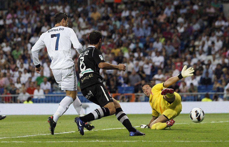 Photo -   Real Madrid's Cristiano Ronaldo from Portugal, left, scores his second goal during a Spanish La Liga soccer match against Granada at the Santiago Bernabeu stadium in Madrid, Spain, Sunday, Sept. 2, 2012. (AP Photo/Andres Kudacki)