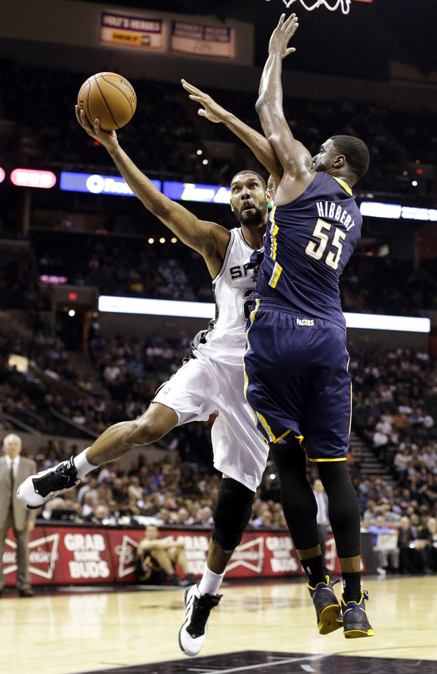 San Antonio Spurs' Tim Duncan, left, shoots around Indiana Pacers' Roy Hibbert (55) during the third quarter of an NBA basketball game, Monday, Nov. 5, 2012, in San Antonio. (AP Photo/Eric Gay)