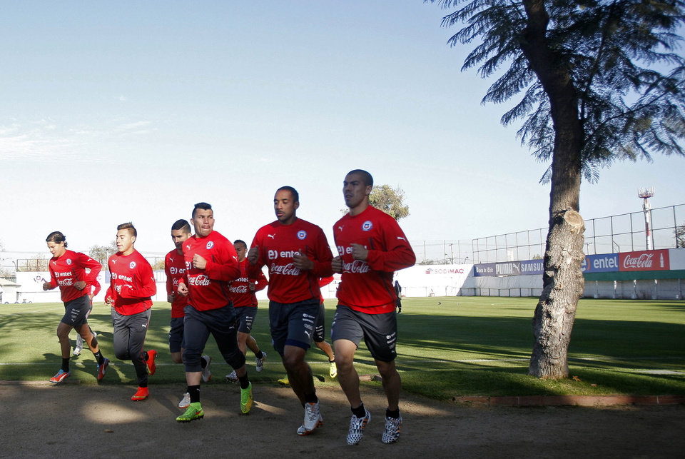Photo - Chile's soccer players warm up during a training session in Santiago, Chile, Wednesday, May 28, 2014. Chile will play a friendly match with Egypt in Santiago on Friday prior to competing at the World Cup in Brazil in June. (AP Photo/Luis Hidalgo)