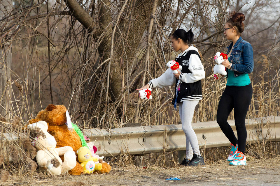 Photo - Dominique Ellison, left, and Rickie Bowling, of Warren, bring stuffed animals to a memorial in honor of their friends who died in a car crash on Park Ave. in Warren, Ohio on Sunday, March 10, 2013. (AP Photo/Scott R. Galvin)