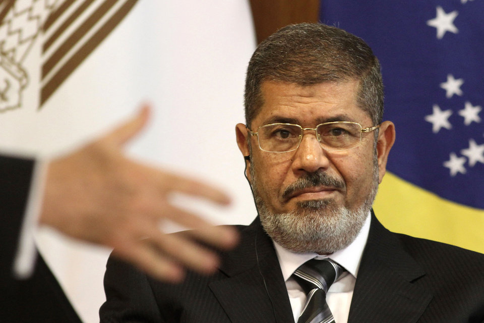 Photo - FILE - In this file photo taken Wednesday, May 8, 2013, Egyptian President Mohammed Morsi attends a bi-lateral signing ceremony with Brazil's president at the Planalto presidential palace in Brasilia, Brazil. An Egyptian court on Sunday, June 23, 2013, said Muslim Brotherhood members conspired with Hamas, Hezbollah and local militants to storm a prison in 2011 and free 34 Brotherhood leaders, including the future President Mohammed Morsi. (AP Photo/Eraldo Peres, File)