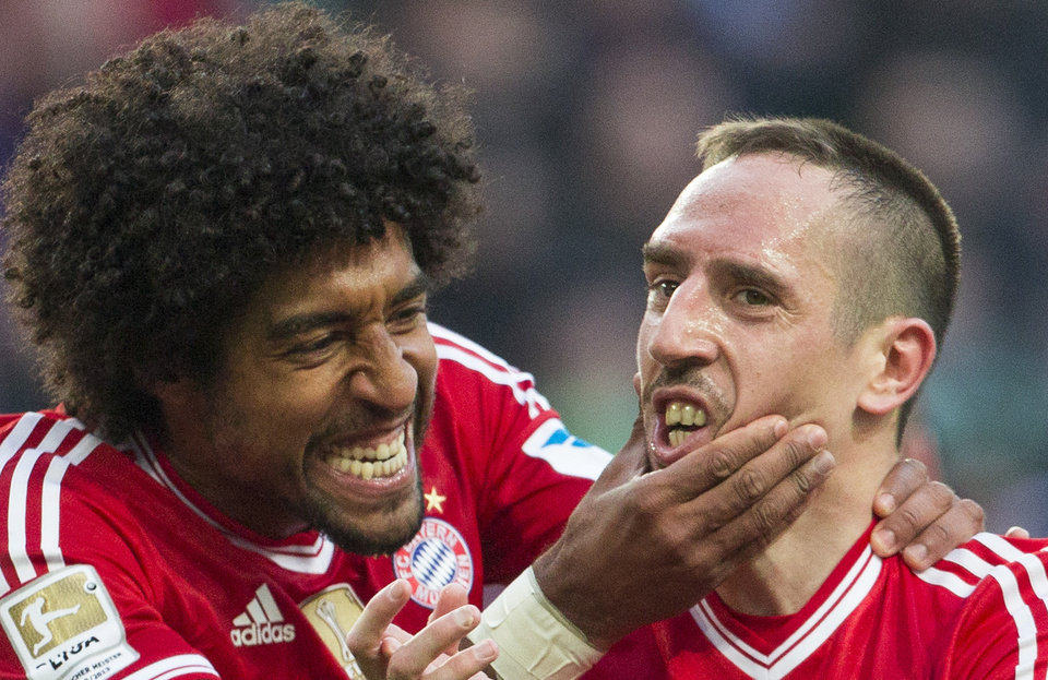 Photo - Bayern's Dante of Brazil, left, and Bayern's Franck Ribery of France celebrate after teammate Arjen Robben scored his side's 4th goal during the German Bundesliga soccer match between VfL Wolfsburg and Bayern Munich in Wolfsburg, Germany, Saturday, March 8, 2014. (AP Photo/Gero Breloer)