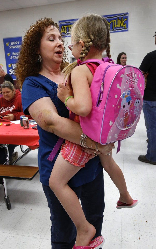 Pre-K teacher Kaye Johnson holds one of her students, Madison Edwards, as they chat on the first time to see each other since the tornado. Edwards is wearing a new backpack that all children were given. There was lots of hugging and plenty of joy at Eastlake Elementary School on SW 134, when Eastlake School hosted a reunion of students, parents, teachers and families from Plaza Towers Elementary School on Thursday, May 23, 2013. Seven students died at Plaza Towers School in Monday\'s EF-5 tornado, which also destroyed the school. Photo by Jim Beckel, The Oklahoman.