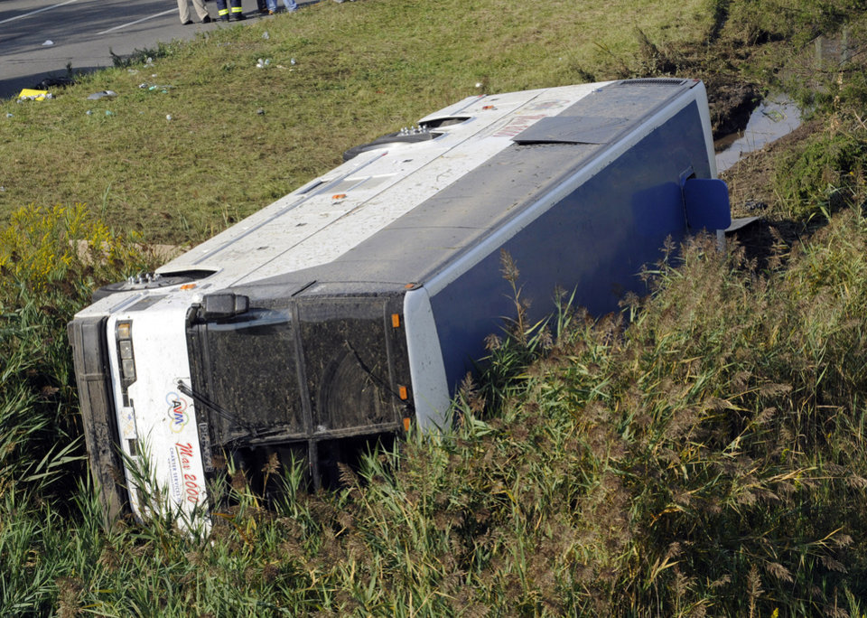A bus sits in a ditch after it overturned coming off an exit ramp on Route 80 in Wayne, N.J. Saturday, Oct. 6, 2012. The chartered tour bus from Toronto carrying about 60 people overturned on an interstate exit ramp. Three people have been taken to hospital with non-life-threatening injuries. (AP Photo/Bill Kostroun)