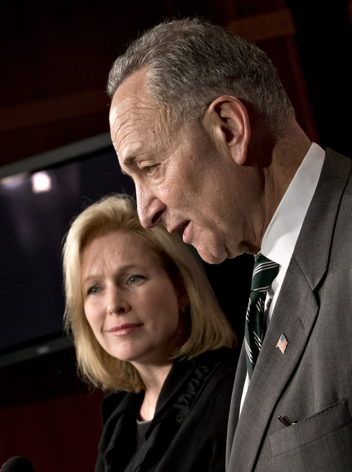 Photo - Sen. Charles Schumer, D-N.Y., right, and Sen. Kirsten Gillibrand, D-N.Y., left, react after the Senate passed a $50.5 billion emergency relief measure for Superstorm Sandy victims at the Capitol in Washington, Monday, Jan. 28, 2013. Three months after Superstorm Sandy devastated coastal areas in much of the Northeast, the Senate is finaly sending a $50.5 billion emergency package of relief and recovery aid to President Obama for his signature. (AP Photo/J. Scott Applewhite)