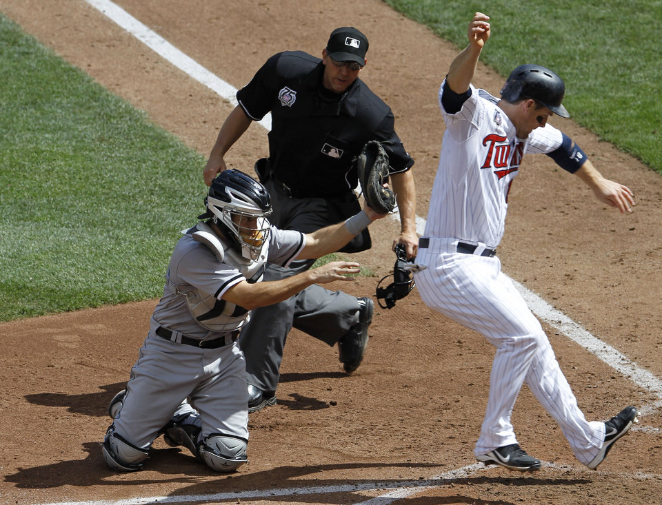 Photo - Minnesota Twins' Josh Willingham, right, scores from third base on a sacrifice fly by Danny Santana as Chicago White Sox catcher Adrian Nieto, left, applies the tag without the ball during the seventh inning of a baseball game in Minneapolis, Sunday, July 27, 2014. Looking to make the call is home plate umpire Jeff Kellogg. The Twins won 4-3. (AP Photo/Ann Heisenfelt)