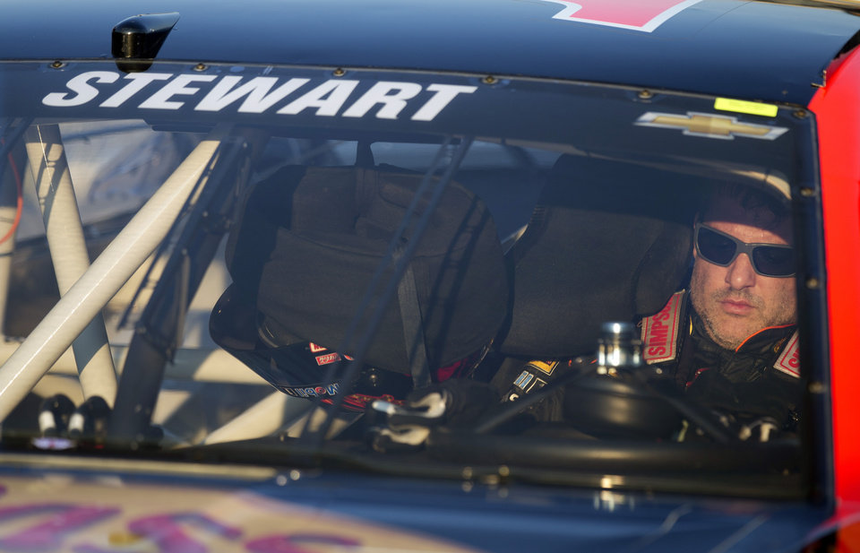 Photo - Sprint Cup Series driver Tony Stewart (14) sits in his car as he waits to qualify for Sunday's Oral B USA 500 NASCAR auto race at Atlanta Motor Speedway Friday, Aug. 29, 2014, in Hampton, Ga. (AP Photo/John Bazemore)