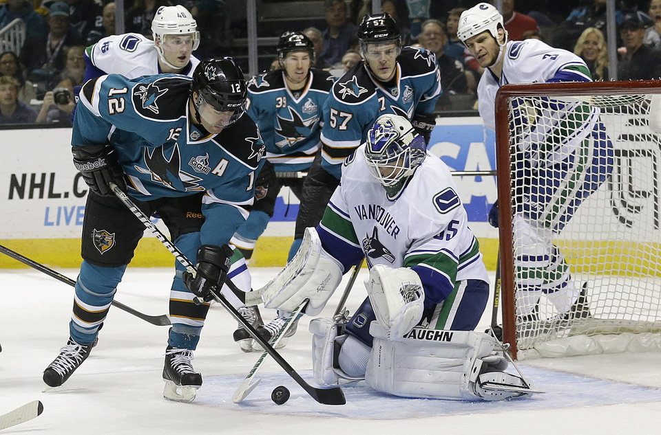 Photo - Vancouver Canucks goalie Cory Schneider (35) defends the goal as San Jose Sharks center Patrick Marleau (12) shoots during the first period of an NHL hockey game in San Jose, Calif., Monday, April 1, 2013. (AP Photo/Jeff Chiu)