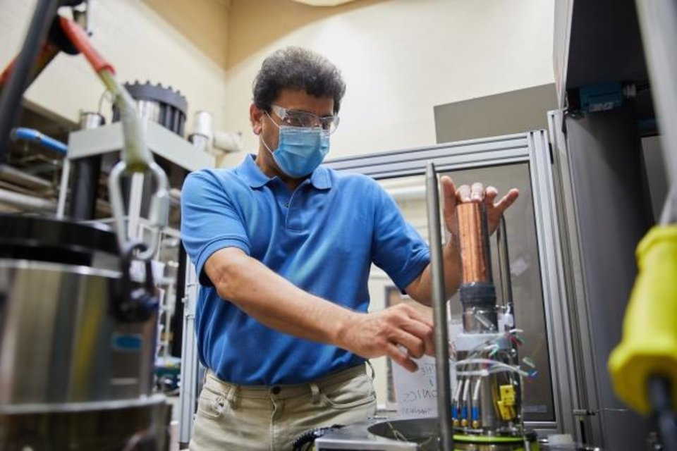 Photo -  Professor Ahmad Ghassemi inserts a core sample into a machine in his laboratory that simulates pressures exerted on rocks deep in the earth. [PROVIDED BY THE UNIVERSITY OF OKLAHOMA]