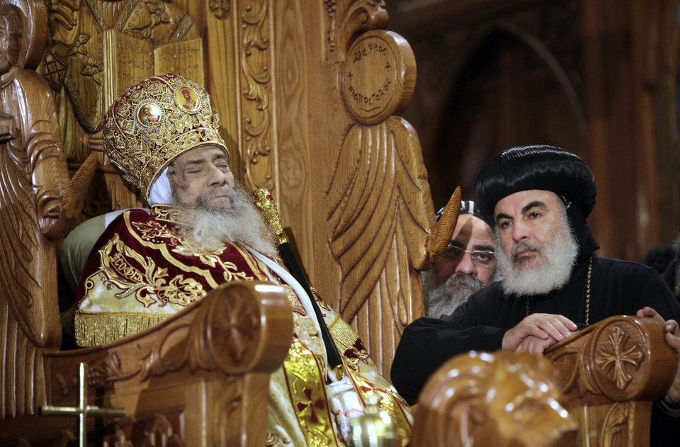FILE -- In this Sunday, March 18, 2012 file photo, Archbishops stand next to the body of Pope Shenouda III seated on the throne of Mar Morqos, or St. Mark, as mourners gather for the viewing of the patriarch at the Coptic Orthodox cathedral in Cairo, Egypt, Sunday, March 18, 2012. Egypt\'s ancient Coptic Christian church named a new pope on Sunday, Nov. 4, 2012 to spiritually guide the community through a time when many fear for their future with the rise of Islamists to power and deterioration in police powers after last year\'s uprising. (AP Photo/Amr Nabil, file)