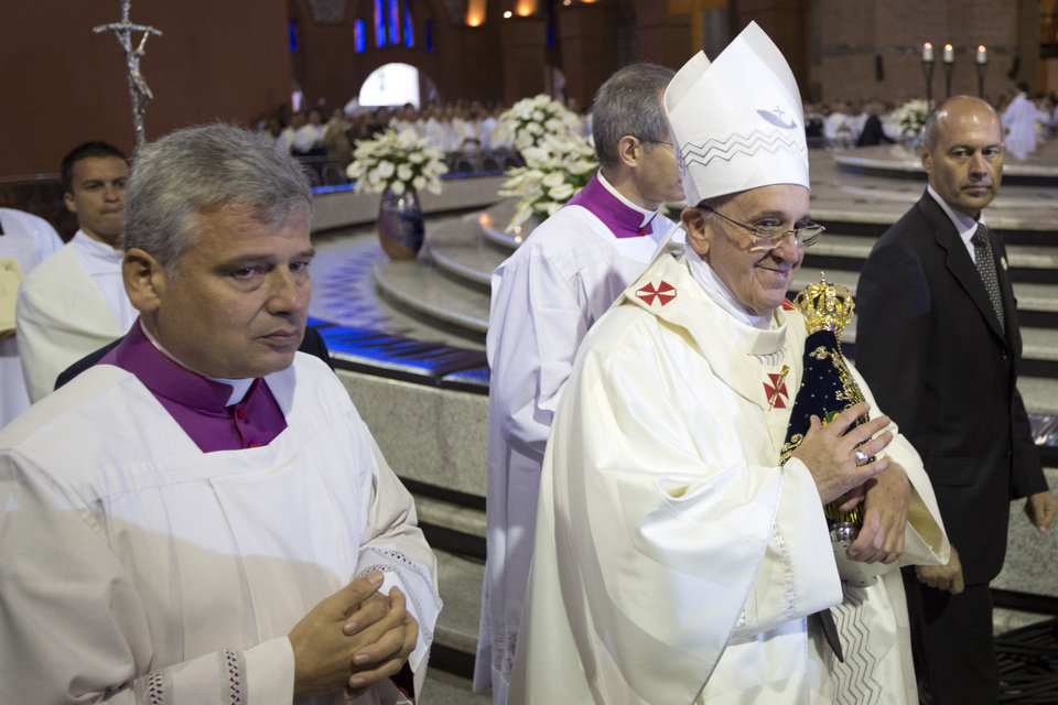 Photo - Pope Francis carries the statue of the Virgin of Aparecida, Brazil's patron saint, at the Aparecida Basilica where he celebrated Mass in Aparecida, Brazil, Wednesday, July 24, 2013. Reverence for the figure of the Virgin Mary runs particularly deep in Latin America. The Vatican says that Pope Francis personally insisted that a trip to the Aparecida Basilica be added to his Brazilian visit agenda. (AP Photo/Felipe Dana)