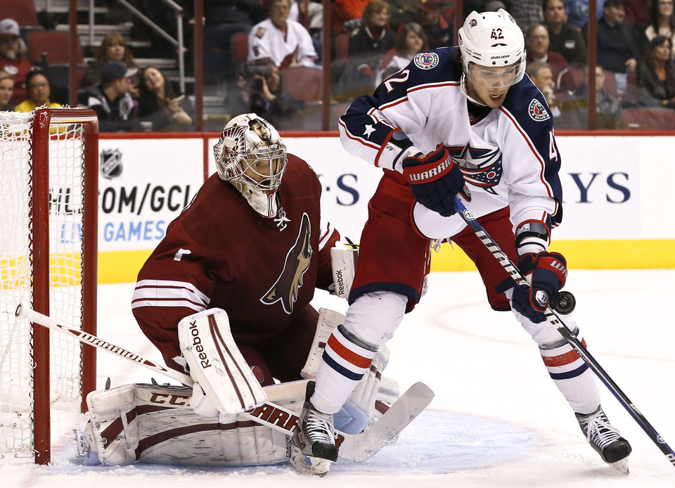 Columbus Blue Jackets' Artem Anisimov (42), of Russia, tries to control the puck in front of Phoenix Coyotes' Jason LaBarbera during the second period in an NHL hockey game on Wednesday, Jan. 23, 2013, in Glendale, Ariz. (AP Photo/Ross D. Franklin)