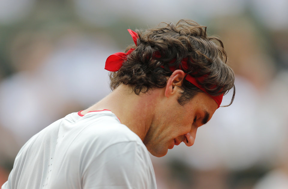 Photo - Switzerland's Roger Federer looks down as he plays Latvia's Ernests Gulbis during their fourth round match of  the French Open tennis tournament at the Roland Garros stadium, in Paris, France, Sunday, June 1, 2014. (AP Photo/David Vincent)