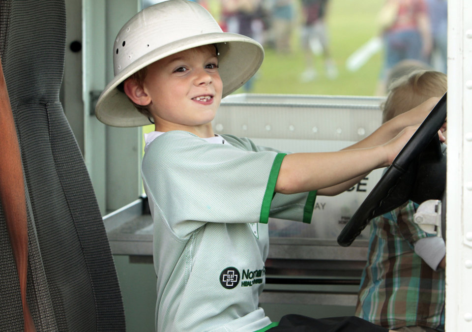 Jackson Hardiman, 7, dons a hat and takes the wheel of a postal truck.