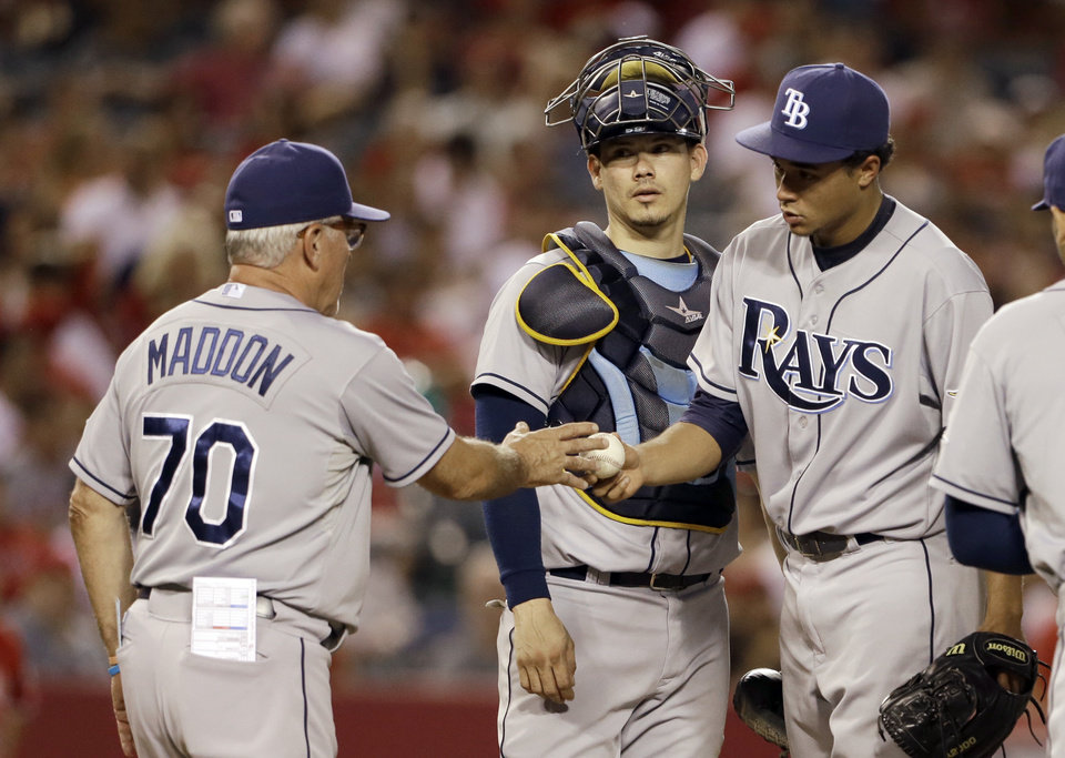Photo - Tampa Bay Rays starting pitcher Chris Archer hands the ball to manager Joe Maddon as catcher Jose Lobaton watches in the fourth inning of a baseball game against the Los Agneles Angels in Anaheim, Calif., Monday, Sept. 2, 2013. (AP Photo/Reed Saxon)