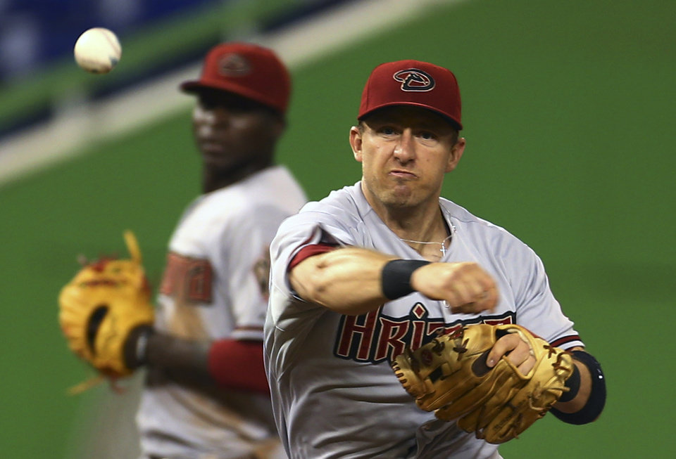 Photo - Arizoina Diamondbacks' Cliff Pennington throws out Miami Marlins' Marcell Ozuna at first during the second inning of a baseball game in Miami, Friday, Aug. 15, 2014. (AP Photo/J Pat Carter)