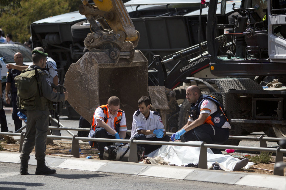 Photo - Israeli medics inspect a body at the scene of an attack in Jerusalem, Monday, Aug. 4, 2014. An Israeli-declared cease-fire and troop withdrawals slowed violence in the Gaza war Monday, though an attack on Israeli bus that killed one person in Jerusalem underscored the tensions still simmering in the region. (AP Photo/Sebastian Scheiner)