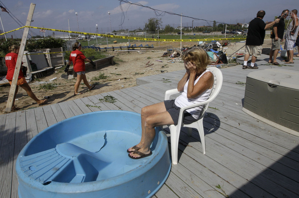 Photo -   Cabana owner Janet Ryan is overcome by emotion as she sits on the porch at the Breezy Point Surf Club in New York, Saturday, Sept. 8, 2012, after a severe weather storm passed the area. A tornado swept out of the sea and hit the beachfront neighborhood in New York City, hurling debris in the air, knocking out power and startling residents who once thought of twisters as a Midwestern phenomenon. Firefighters were still assessing the damage, but no serious injuries were reported and the area affected by the storm appeared small. (AP Photo/Kathy Willens)