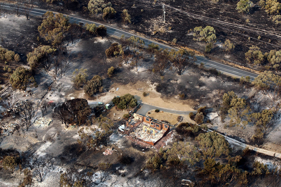 Photo - This aerial photo shows homes destroyed by a wildfire between Dunalley and Boomer Bay, east of the Tasmanian capital of Hobart, Australia, on Saturday, Jan. 5, 2013.   Australian officials battled a series of wildfires amid scorching temperatures across the country on Saturday, with one blaze destroying dozens of homes in the island state of Tasmania. (AP Photo/Chris Kidd, Pool)