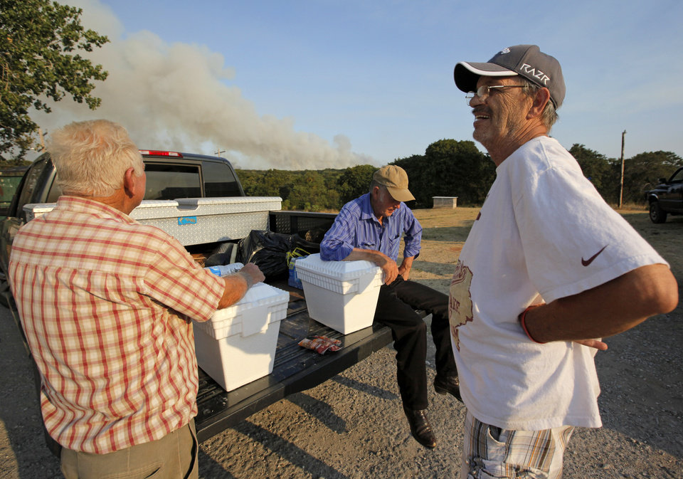 Photo - From left, Gayland Cannon, Eugene Hacker and Ron Ross wait at a gas station at SE108 and Hwy 9 after evacuating their homes in the area of SE 132nd and Cedar Lane as a wildfire burns through Cleveland County near Norman, Okla., Friday, Aug. 3, 2012. Photo by Nate Billings, The Oklahoman