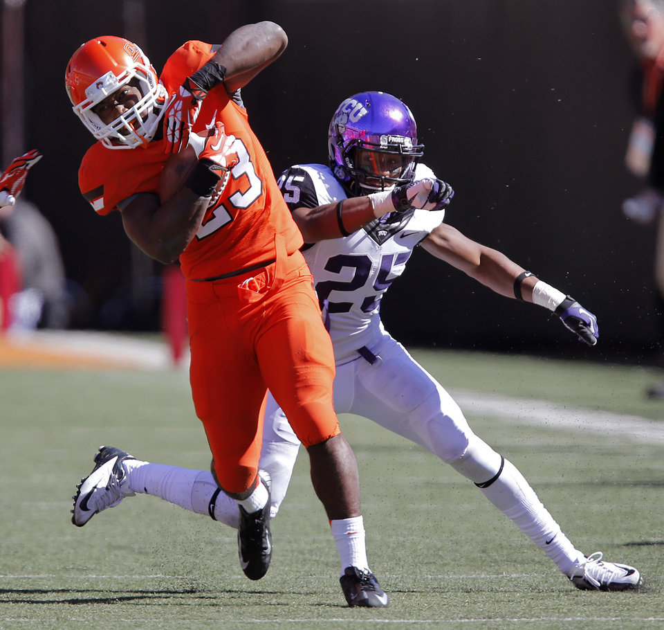 Oklahoma State\'s Rennie Childs (23) make a catch in front of a TCU defender during a college football game between the Oklahoma State University Cowboys (OSU) and the Texas Christian University Horned Frogs (TCU) at Boone Pickens Stadium in Stillwater, Okla., Saturday, Oct. 19, 2013. Photo by Chris Landsberger, The Oklahoman
