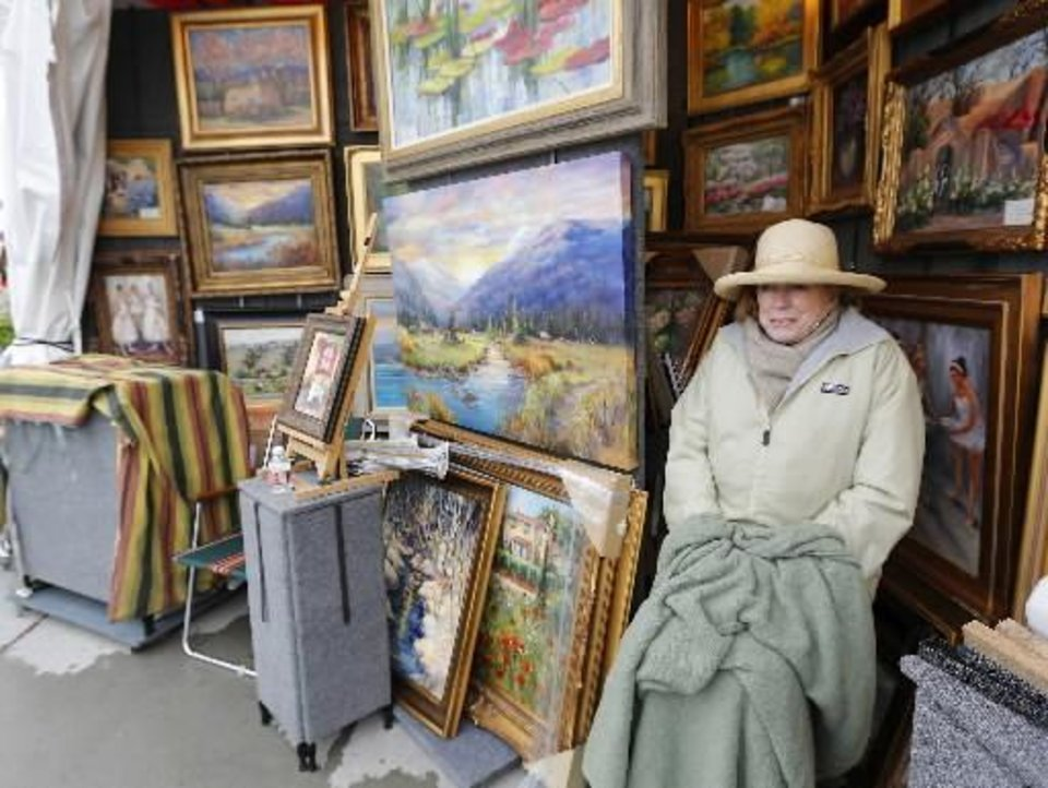 ulsa artist J. Matzdorf keeps warm in her booth at the Festival of the Arts in Oklahoma City , Tuesday April 23, 2013. Photo By Steve Gooch, The Oklahoman