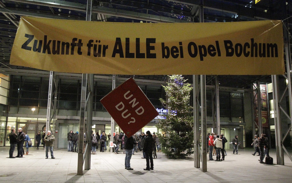 "Opel employees queue for a staff meeting in Bochum, Germany, Monday, Dec. 10, 2012. The poster reads:' Future for all at Opel Bochum' with sign hanging under reading ""And You?"".  Opel announced plans today to stop car production in Bochum in 2016. But Opel says the company's warehouse in Bochum will continue to employ people after 2016 and may be expanded. The company also is negotiating with employee representatives to produce components at the site. (AP Photo/Frank Augstein)"