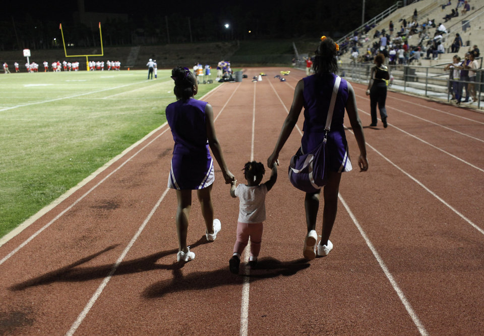 Cheerleaders escort a young girl back before the halftime ends at the Northwest Classen vs. Western Heights high school football game at Taft Stadium Thursday, September 20, 2012. Photo by Doug Hoke, The Oklahoman