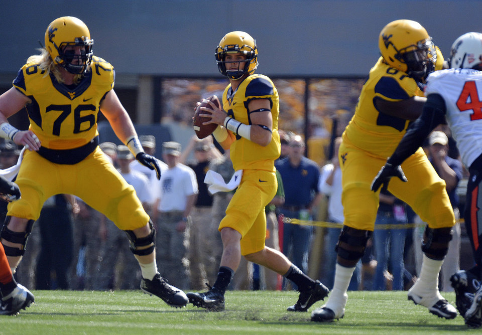 West Virginia quarterback Clint Trickett (9) looks for an open receiver during the first quarter of an NCAA college football game against Oklahoma State in Morgantown, W.Va., on Saturday, Sept. 28, 2013. (AP Photo/Tyler Evert) ORG XMIT: WVTE104