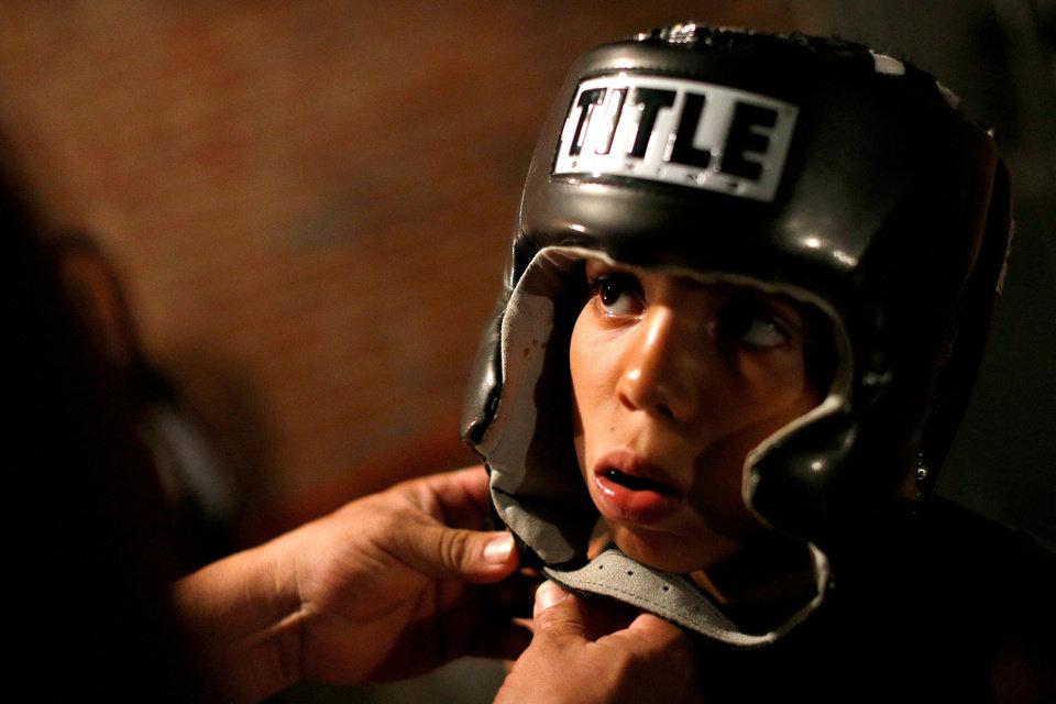 Photo -  Chris Barba, 9, of Edmond, gets help with his headgear before his first fight at The Underground Arena in Oklahoma City, Saturday, June 15, 2013. Photo by Bryan Terry, The Oklahoman