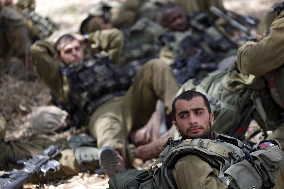 Photo - Israeli infantry soldiers rest before walking to their armored personnel carriers to move to a new position on the Israel-Gaza border, Saturday, July 12, 2014. Israeli airstrikes targeting Hamas in Gaza hit a mosque its military says concealed the militant group's weapons, as the Palestinian death toll topped 120 Saturday in an offensive that showed no signs of slowing down. Israel launched its campaign five days ago to stop relentless rocket fire on its citizens. While there have been no fatalities in Israel, Palestinian officials said overnight attacks raised the death toll there to over 120, with more than 920 wounded. (AP Photo/Lefteris Pitarakis)