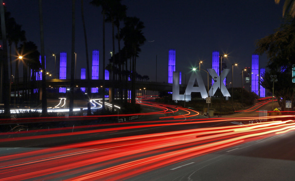 Photo - FILE - In this Nov. 2, 2013 file photo, lighted pylons at the Century Boulevard entrance to Los Angeles International Airport, which normally flash in a multicolored sequence, shine a steady blue in honor of Gerardo Hernandez, the Transportation Security Administration officer slain at an LAX terminal the day before. Two armed police officers assigned to guard a Los Angeles airport terminal where a gunman killed a screener in Nov. 2013, left for breaks without informing dispatchers as required minutes before the gunfire erupted. (AP Photo/Reed Saxon)