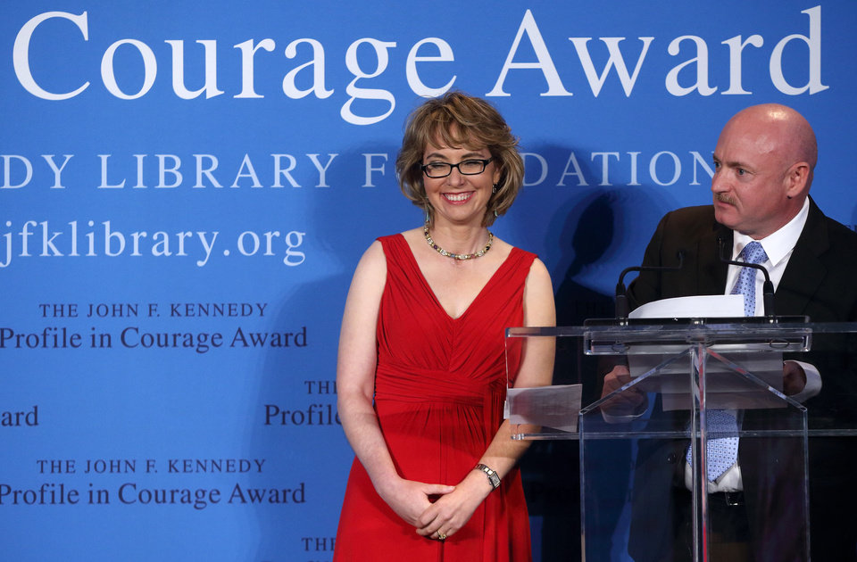 Photo - Former Arizona congresswoman Gabrielle Giffords, left, stands with her husband Capt. Mark Kelly after receiving the John F. Kennedy Profile in Courage Award in Boston, Sunday, May 5, 2013. (AP Photo/Michael Dwyer)