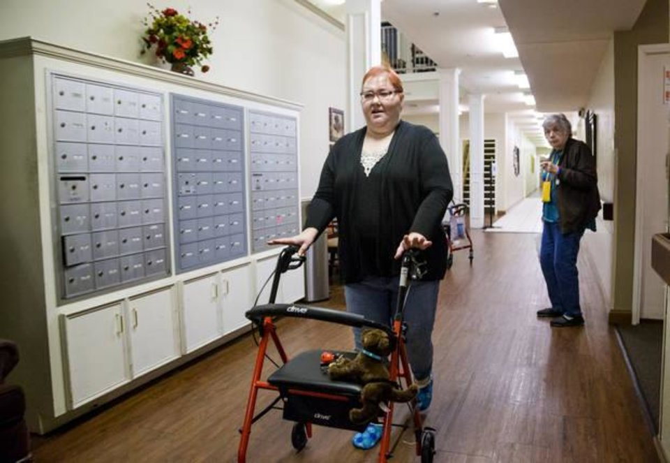 Photo -  Dana Dixon walks down the hallway at Heritage Assisted Living Center in Yukon. [Photo by Chris Landsberger, The Oklahoman]