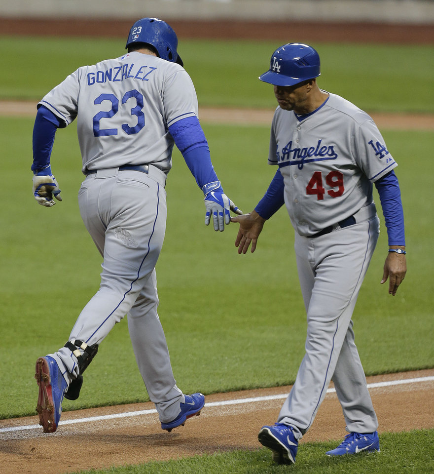 Photo - Los Angeles Dodgers' Adrian Gonzalez (23) is greeted by third base coach Lorenzo Bundy as he rounds the bases after hitting solo home run against the New York Mets during the second inning of a baseball game, Wednesday, May 21, 2014, in New York. (AP Photo/Julie Jacobson)