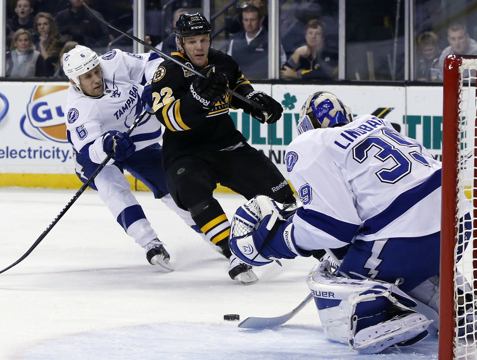 Photo - Tampa Bay Lightning goalie Anders Lindback (39) makes a save against an attempt by Boston Bruins right wing Shawn Thornton (22) as defenseman Sami Salo (6) defends during the second period of an NHL hockey game in Boston Monday, Nov. 11, 2013. The Bruins won 3-0. (AP Photo/Elise Amendola)