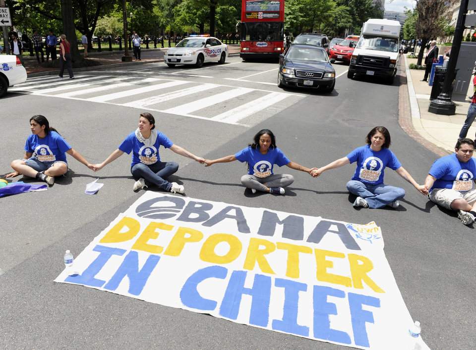 Photo - FILE - This June 5, 2014 file photo shows protestors blocking traffic near the White House in Washington in response to President Obama's decision to delay the deportation review he ordered from the Department of Homeland Security. To the frustration of many of his supporters, President Barack Obama is backing away from actions he could take unilaterally on immigration. Instead, he is kicking the issue to House Republicans despite mounting evidence they won't address the millions of immigrants living illegally in the US. (AP Photo/Susan Walsh, File)