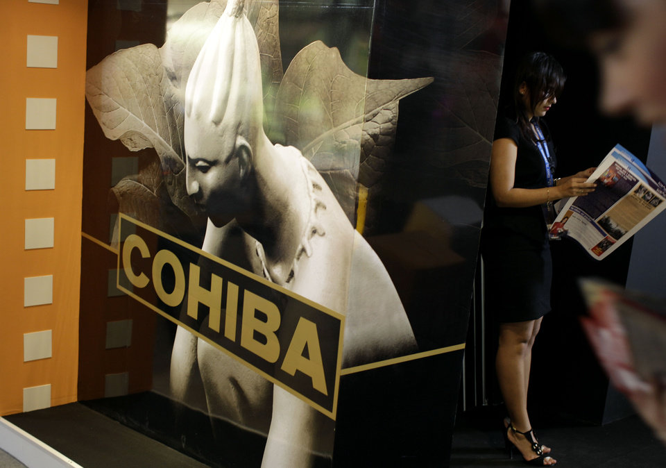 In this picture taken Monday Nov. 5, 2012 a woman reads a newspaper next to the stand of Cohiba during the 30th Havana International Fair in Havana, Cuba. Many of America's best-known brands were on display at a Havana exposition center this past week as representatives hawked some of the few U.S. products that can legally be exported to Cuba, thanks to an exception to the U.S. embargo allowing cash-up-front sales of food, agricultural goods and medicine.(AP Photo/Franklin Reyes)