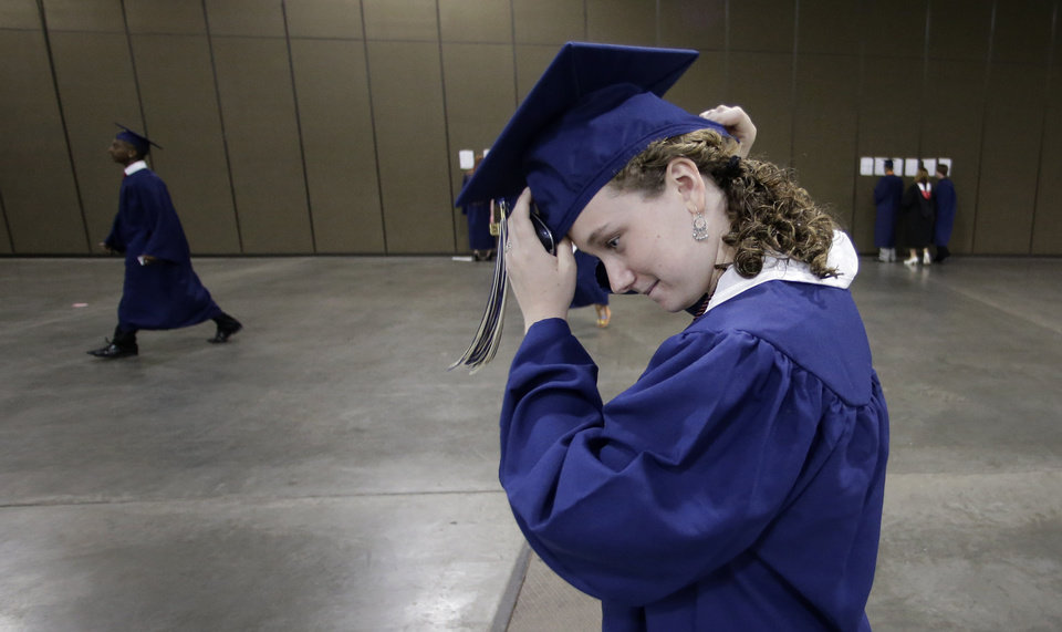 Photo - Southmoore High School senior Miranda Mann adjusts her mortar board as she get ready to attend her commencement ceremony in Oklahoma City, Saturday, May 25, 2013, five days after a tornado wreaked havoc in their attendance area, in Moore, Okla. Mann's home was among those destroyed after a huge tornado roared through the Oklahoma City suburb Monday, flattening a wide swath of homes and businesses. (AP Photo/Charlie Riedel)