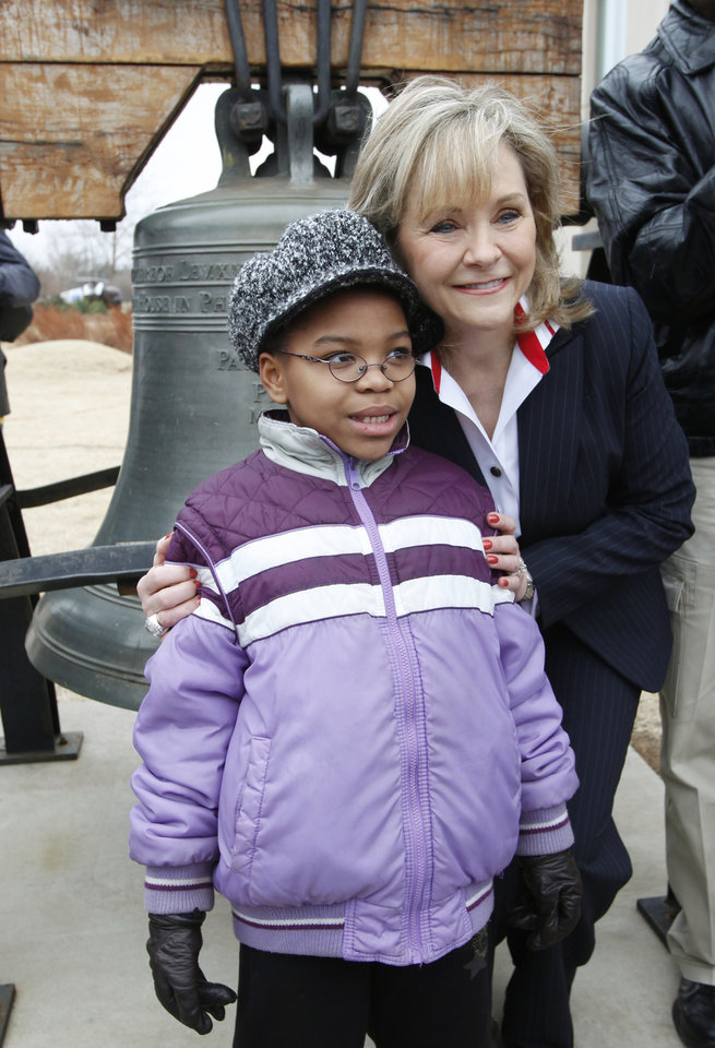 Photo - Gov. Mary Fallin poses for a photo with Lauren Wilson, 7yr.  with a Liberty Bell, replica outside the Oklahoma History Center during a Martin Luther King Day ceremony in Oklahoma City, January 17 , 2011. Photo by Steve Gooch, The Oklahoman